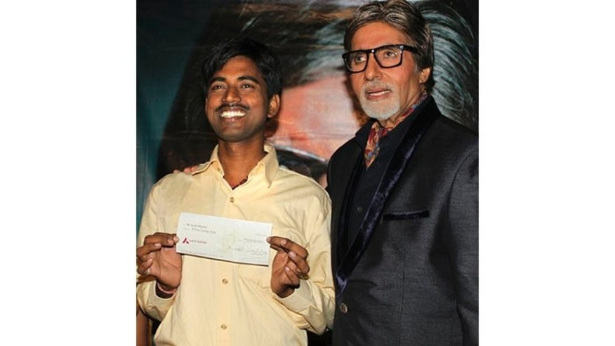 October 25: Sushil Kumar, left, with Bollywood actor Amitabh Bachchan, shows $1 million check after winning on an Indian game show, in Mumbai, India.
