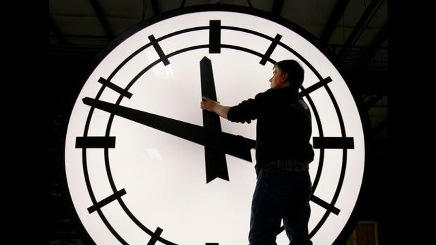 Electric Time machinist Scott Gow prepares to remove the hands of an eight-foot clock being shipped to the Ashley Furniture company in Kenosha, Wis., at the Electric Clock factory in Medfield Mass., Friday morning, March 9, 2007. Daylight saving time begins Sunday morning March 11, 2007, three weeks earlier than it has for the past two decades due to a 2005 law taking effect this year. (AP Photo/Stephan Savoia)