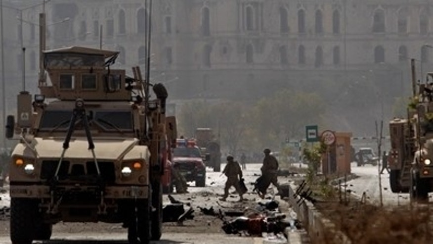 Oct. 29, 2011: US soldiers walk at the site of a suicide car bomber in Kabul, Afghanistan