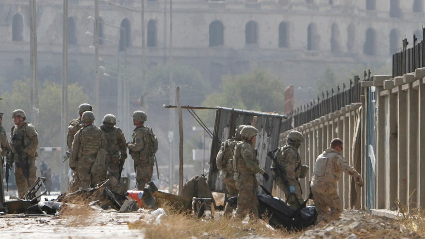 Oct. 29, 2011: US soliders, right, carry a body from the site of a suicide car bomber in Kabul, Afghanistan.