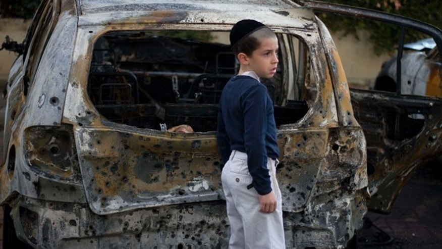 Oct. 30, 2011: A boy stands next to a burned cars following Saturday night's rocket attacks from the Gaza Strip, in Ashdod, southern Israel.