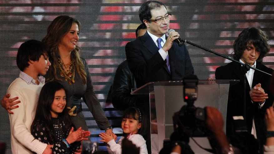 Gustavo Petro speaks to supporters after winning Bogota's mayoral race as his family stands with him in Bogota, Colombia, Sunday Oct. 30, 2011. Voters on Sunday elected Gustavo Petro as mayor of Bogota, the first time an ex-guerrilla has won Colombia's second most important elected office.  (AP Photo/Fernando Vergara)