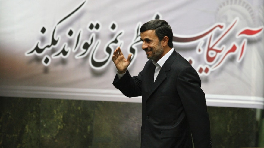 "Nov. 2, 2011: Iranian President Mahmoud Ahmadinejad, waves, as he arrives to attend an open session of parliament for impeachment of his Economy Minister, Shamsoddin Hosseini, unseen, as a banner hangs behind him with a quotation of late revolutionary founder Ayatollah Khomeini, which says ""US can not do anything"", in Tehran, Iran."