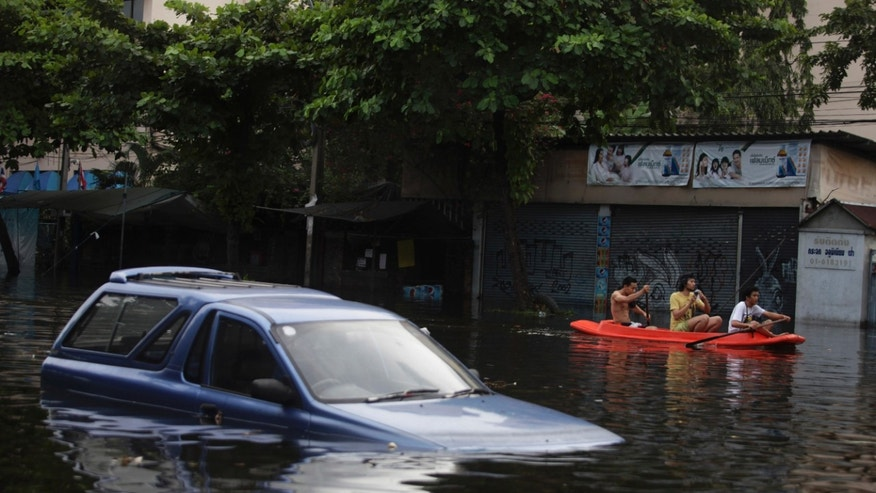 Oct. 28, 2011: Thai men row their boat past a vehicle submerged in floodwaters in Bangkok, Thailand.