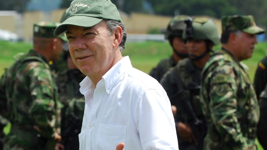 Colombia's President Juan Manuel Santos greets journalists at a military base where he spoke to and shook hands with soldiers who took part in the operation that led to the death of Alfonso Cano, 63, the top leader of the Revolutionary Armed Forces of Colombia, FARC, in Popayan, Colombia, Saturday Nov. 5, 2011. Cano was killed in a military raid in a remote area of the southwestern state of Cauca. The rebel leader's body was taken to a morgue in Popayan.  (AP Photo/Carlos Julio Martinez)