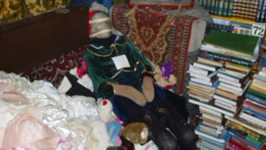 This photo provided by the Russian Interior Ministry's branch in the Nizhny Novgorod region shows a mummified body at an apartment dressed up like a doll taken from a grave at an apartment in Nizhny Novgorod, some 250 miles east of Moscow. Police arrested a local man who had this and 28 other such dolls made of human remains at his home.