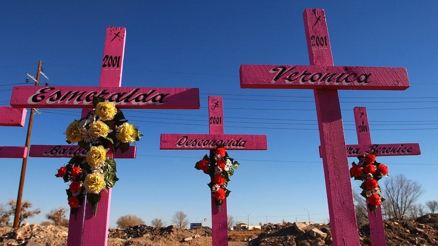 FILE - In this Jan. 30, 2004 file photo, crosses with names painted on them stand at the spot where the bodies of eight young women were found in 2001 in Ciudad Juarez, Mexico.