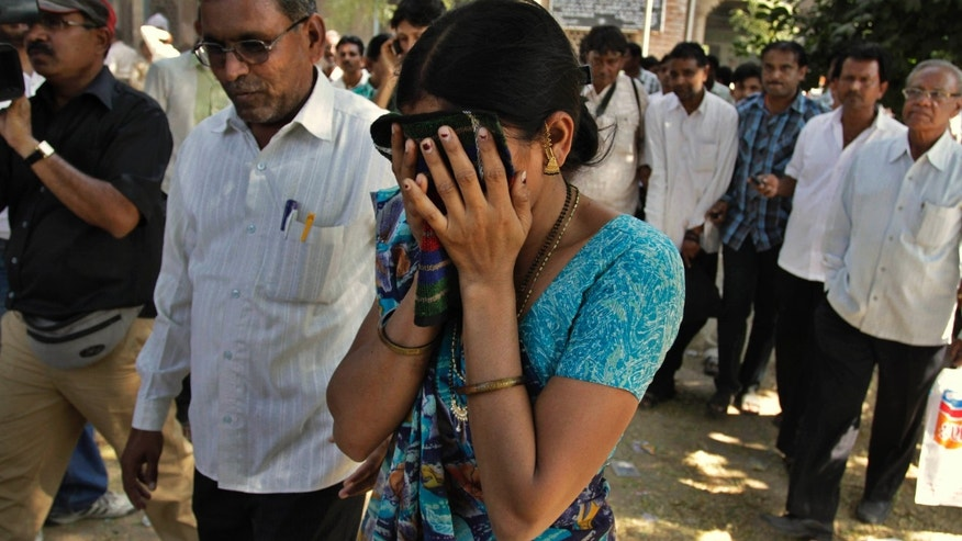 Nov. 9, 2011: An unidentified relative of one of the convicted Hindus breaks down upon hearing the verdict at the district court in Mehsana, about 25 miles north of Ahmadabad, India.