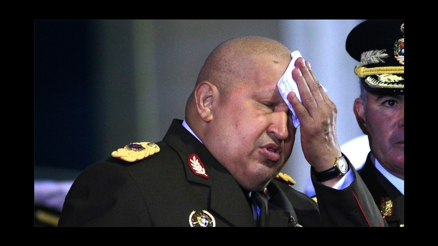 Venezuela's President Hugo Chavez, left, wipes the sweat at his forehead during a ceremony at the military academy in Fuerte Tiuna, Caracas, Venezuela, Sunday, Nov. 6, 2011. At right is Venezuela's Defense Minister Gen. Carlos Mata.  (AP Photo/Ariana Cubillos)