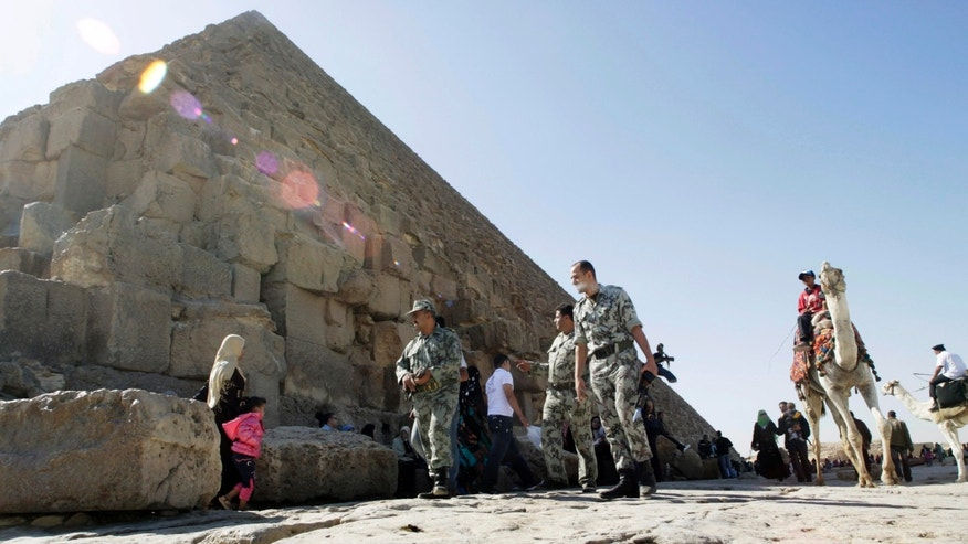 Nov. 11, 2011: Egyptian soldiers walk at the base the pyramid of Khufu, largest of the Giza Pyramids in Cairo, Egypt.