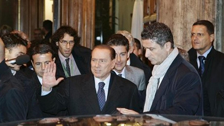 November 10, 2011: Italian Premier Silvio Berlusconi, center, leaves at the end of a meeting with his allies in the Italian Senate in Rome.