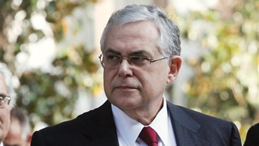 November 10, 2011: Greece's new Prime Minister Lucas Papademos arrives to deliver a statement outside the presidential palace in Athens.