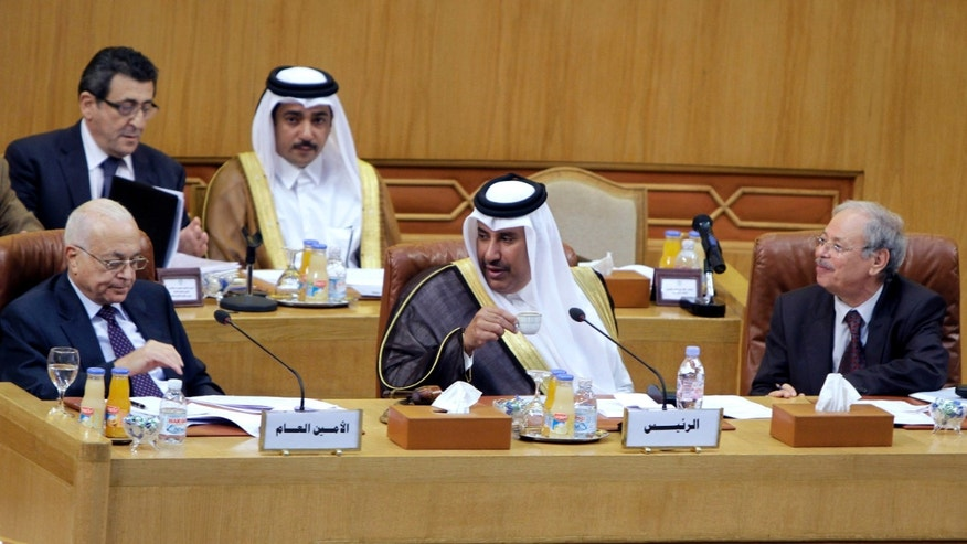 Nov. 12, 2011: Qatari Foreign Minister Hamad bin Jasim, center, looks at Arab League secretary-general Nabil al-Arabi Nabil, left, during an Arab League emergency session on Syria at the Arab League headquarters in Cairo, Egypt.