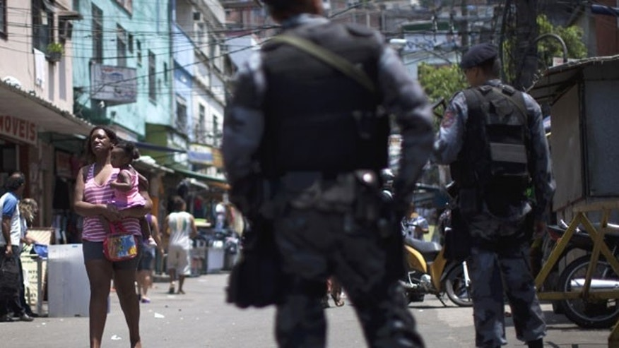 November 11, 2011: A woman holding a baby walks past officers as they patrol an entrance to Rocinha slum in Rio de Janeiro, Brazil.