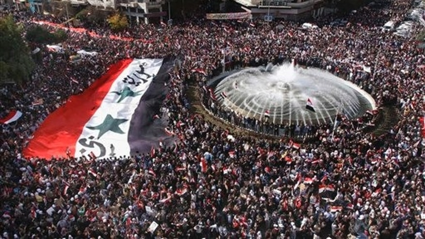 Nov. 13, 2011: Pro-Syrian regime protesters, carry a giant Syrian flag during a demonstration against the Arab League decision to suspend Syria, in Damascus, Syria. Tens of thousands of pro-regime demonstrators gathered in a Damascus square Sunday to protest the Arab League's vote to suspend Syria over its bloody crackdown on the country's eight-month-old uprising.