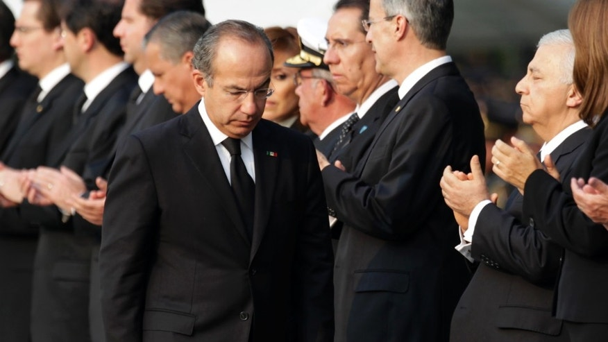 Mexico's President Felipe Calderon walks after paying his respects to the relatives of the eight victims of a helicopter crash at the Campo de Marte military field in Mexico City, Thursday, Nov. 12, 2011. Mexico's Interior Minister Francisco Blake Mora and seven others died Friday in the accident in a mountainous area southeast of Mexico City. (AP Photo/Eduardo Verdugo)