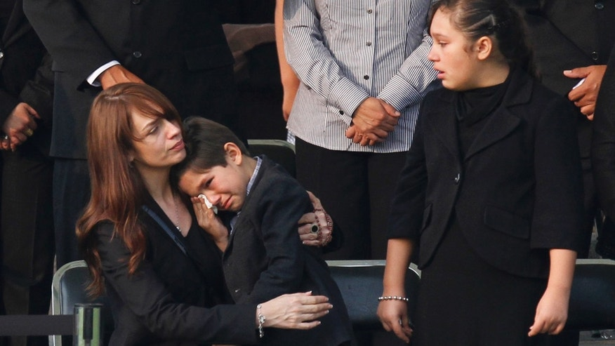 Gloria Cossio, widow of Mexico's Interior Minister Francisco Blake Mora, left, comforts her son Jose Francisco as her daughter Gloria looks on during her husband's funeral service at the Campo de Marte military field in Mexico City, Saturday, Nov. 12, 2011. Blake Mora died Friday in a helicopter crash with seven others at a mountainous area southeast of Mexico City. (AP Photo/Marco Ugarte)