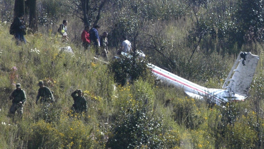 Soldiers and investigators examine the wreckage of a helicopter that was carrying Mexico's Interior Minister Francisco Blake Mora, at a mountainous area in Santa Catarina Ayatzingo, southeast of Mexico City, Friday, Nov. 11, 2011. The Mexican government said Friday, that Mora, Mexico's No. 2 government official next to the president, died in the helicopter crash with seven others, including the pilot. (AP Photo)