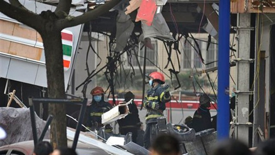 Rescuer workers go through the aftermath of an explosion at a ground floor restaurant in Xi'an in northwest China's Shaanxi province Monday Nov. 14, 2011.