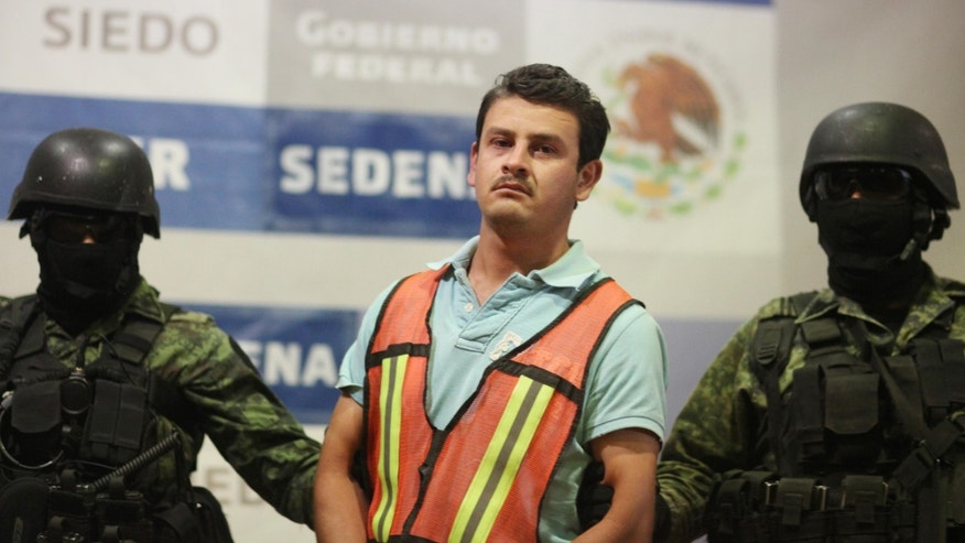"Juan Gabriel Orozco Favela, alias ""El Gasca"" alleged member of the Knights Templar drug cartel, is escorted by Mexican Army soldiers as he is presented to the media in Mexico City, Tuesday Nov. 15, 2011. The Defense Department says Orozco Favela was in charge of smuggling drugs through the Michoacan state capital of Morelia for the quasi-religious gang, which is known as a major trafficker of methamphetamine. Officials say Orosco Favela, who was arrested Sunday, was responsible for the deaths of 21 people who were tortured and hanged or drowned and dumped around the outskirts of Morelia in June. (AP Photo/Alexandre Meneghini)"