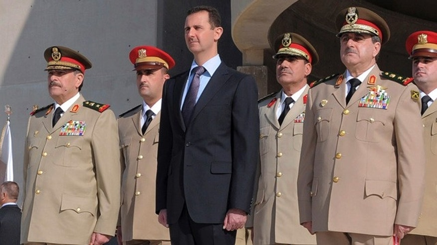 Oct. 6: Syrian President Bashar Assad, center,  stands next to Syrian Defense Minister Gen. Dawoud Rajha, right, and Chief of Staff Gen. Fahed al-Jasem el-Freij, left, during a ceremony to mark the 38th anniversary of the October 1973 Arab-Israeli war, in Damascus, Syria.