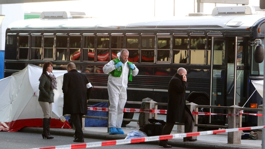 March 2, 2011 file photo police investigate the scene after a gunman fired shots at U.S. soldiers on the bus outside Frankfurt airport, Germany. A 21-year-old Kosovo Albanian charged with the fatal shooting of two U.S. airmen outside Frankfurt airport will go on trial, Wednesday, Aug. 31, 2011.