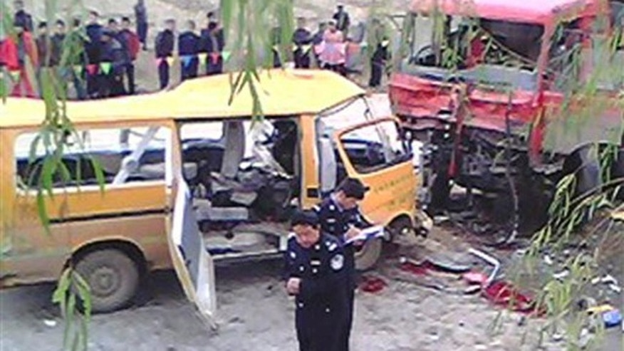 November 16, 2011: In this photo taken on a mobile phone, two police officers, front, investigate at the accident scene where a kindergarten minibus, left, collided head-on with a truck loaded with coal, right, on a road at Yu Linzi township in Qingyang.