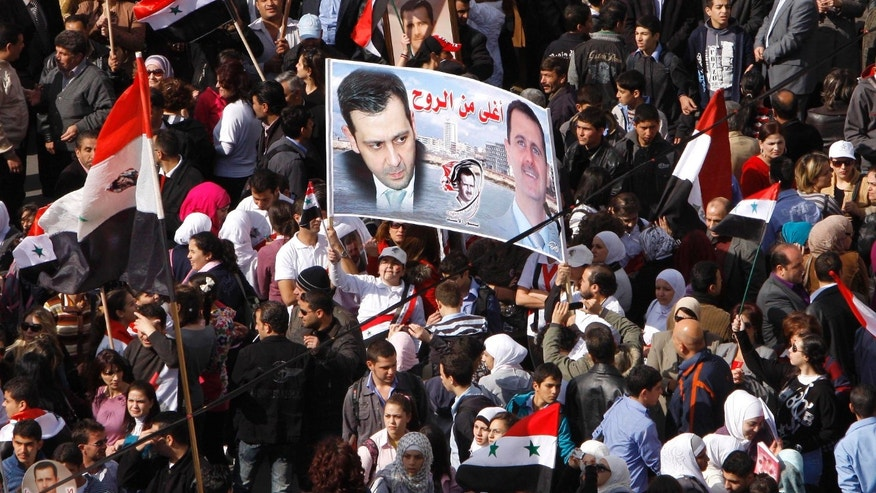 "Nov. 13, 2011: Pro-Syrian regime protesters, hold a poster showing Syrian President Bashar Assad, right, and his brother Maher, left, with Arabic words: ""dearer than the spirit,"" during a demonstration against the Arab League decision to suspend Syria, in Damascus, Syria."