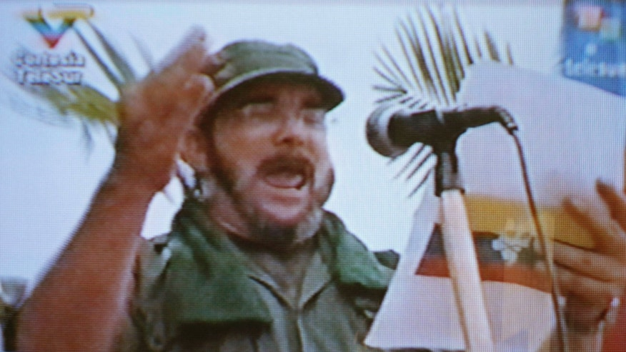 FILE - In this undated video image broadcast by the Venezuela-based Telesur network, Timoleon Jimenez, a senior commander of the Revolutionary Armed Forces of Colombia (FARC) reads a statement in an unknown location in Colombia. The ruling junta of Colombia's main rebel group designated the 52-year-old as the new chief on Nov. 5, a day after the top guerrilla commander Alfonso Cano was killed in southwestern Colombia.  (AP Photo, File)