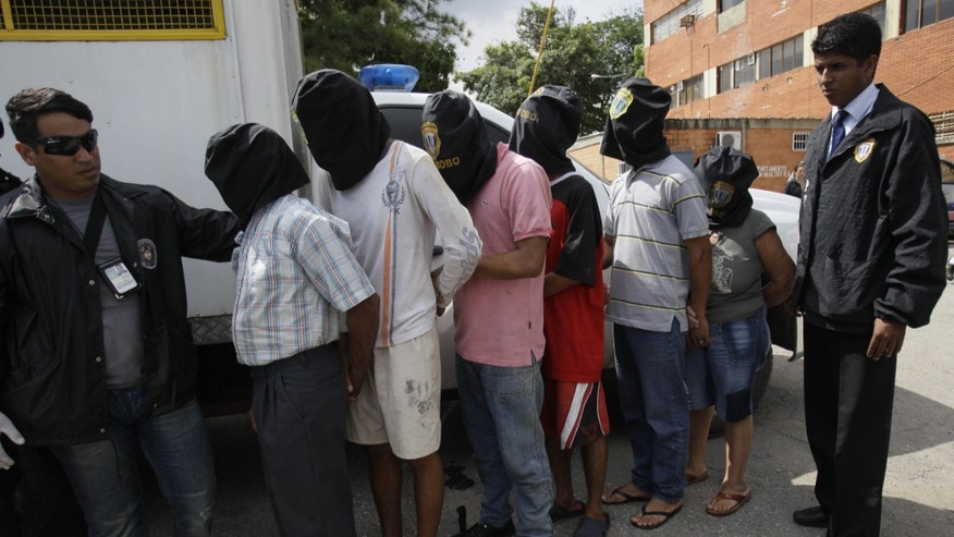 The alleged kidnappers of Washington Nationals catcher Wilson Ramos are presented to the media in the parking lot of the Venezuela's Judicial Police headquarters in Valencia, Venezuela.