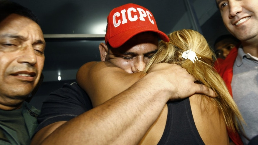 Washington Nationals' catcher Wilson Ramos is hugged by a relative at the Criminal Police ( CICPC ) headquarters  in Valencia, Venezuela, Saturday, Nov. 12, 2011. Venezuelan police commandos rescued Ramos and arrested three of his abductors Friday, two days after he was kidnapped.  At right is Venezuela's Justice Minister Tareck El Aissami.(AP Photo/Lexander Loiza)