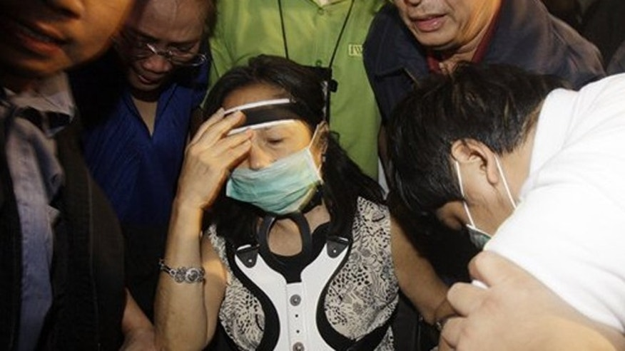 November 15, 2011: Former Philippine President and current member of Congress Gloria Macapagal Arroyo, center, is assisted by her aides as they leave the airport in Manila, Philippines.