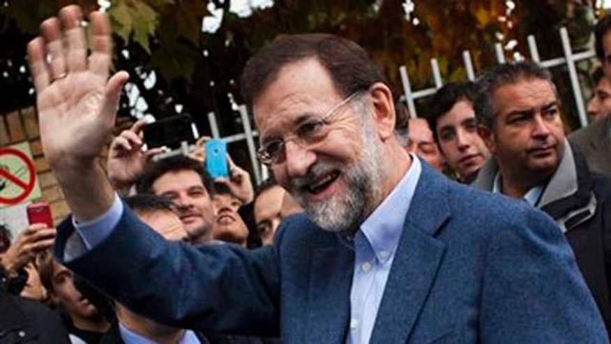 Conservative Popular Party candidate Mariano Rajoy waves after voting at a voting station in Madrid, Sunday Nov, 20, 2011.