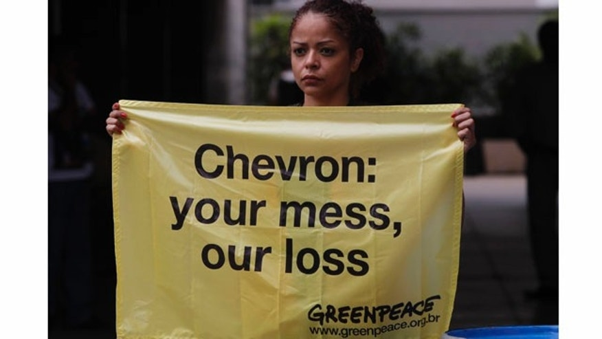 "A Greenpeace activist holds a sign that reads in Portuguese ""Chevron, your mess, our loss"" as she protests an oil spill in an offshore field operated by Chevron Corp, outside Chevron's offices in Rio de Janeiro, Brazil, Friday Nov. 18, 2011. The Brazilian Federal Police on Thursday began investigating an oil spill in an offshore field operated by Chevron Corp., a leak that an environmental group alleges is far bigger than the company has stated.  The leaking well is part of the Chevron-operated Frade project, located underwater off the northeastern coast of Rio de Janeiro state. (AP Photo/Silvia Izquierdo)"