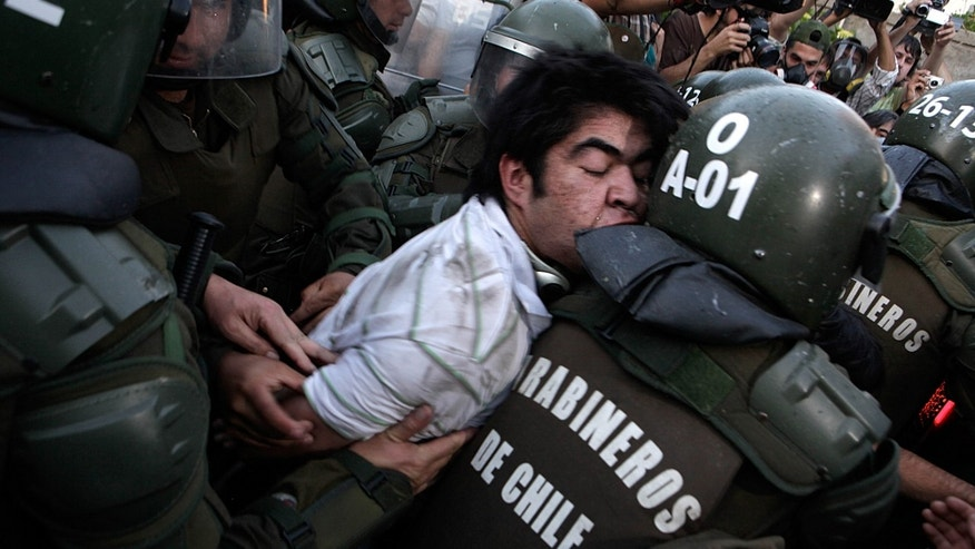 Police officers detain a human rights activist after clashes during an event honoring  Miguel Krassnoff, a former Chilean army brigadier during the 1973-1990 dictatorship of August Pinochet, in Santiago, Chile, Monday, Nov. 21, 2011. Krassnoff is currently serving a 144-year sentence for homicide and forced disappearances.  (AP Photo/Luis Hidalgo)