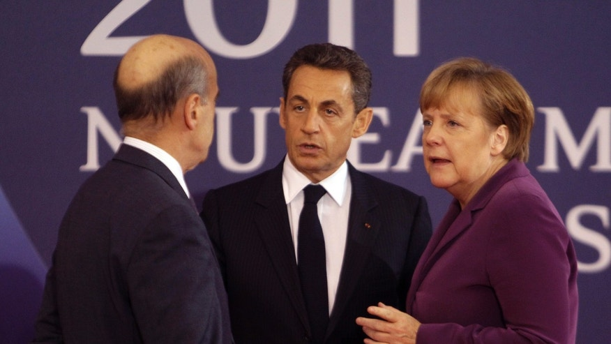 Nov. 2, 2011: French President Nicolas Sarkozy, center, and French Foreign Minister Alain Juppe, left, welcome German Chancellor Angela Markel at the G20 summit in Cannes.