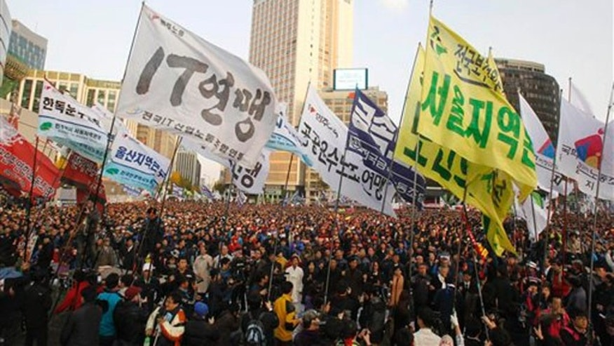 About 20,000 members of the Korean Confederation of Trade Unions carry their union flags during a rally to oppose ratification of the South Korea-U.S. free trade agreement in front of the Seoul City Hall, South Korea, Sunday, Nov. 13, 2011.
