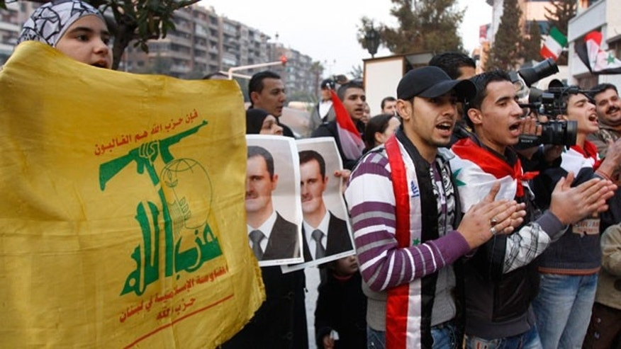 Nov. 24, 2011: Pro-Syrian regime protesters hold Hezbollah flags and shout pro-Syrian President Bashar Assad slogans during a protest in front the Iranian embassy to thank Iran for their support of the Syrian regime, in Damascus, Syria.