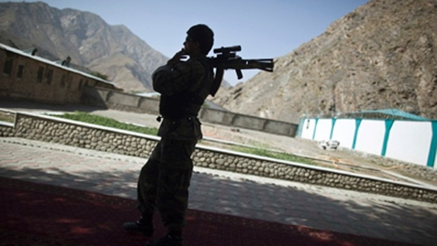 FILE 2011: An Afghan security personnel holds his rifle as he keeps watch during  the security handover ceremony in Panjshir province.