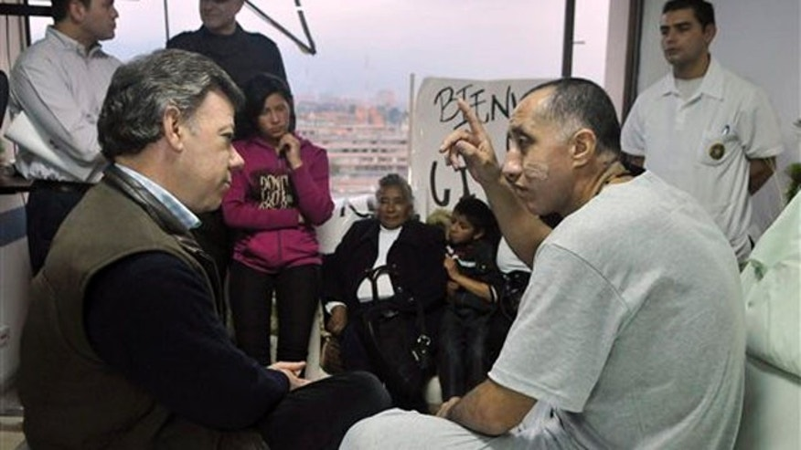 In this photo released by the Presidency of Colombia, President Juan Manuel Santos, left, listens to survivor rebel hostage police Sgt. Luis Alberto Erazo at a military hospital in Bogota, Colombia, Sunday Nov. 27, 2011. Guerrillas of the Revolutionary Armed Forces of Colombia, FARC, executed four of its longest-held captives Saturday in the jungles of the southern state of Caqueta. Erazo, who was with them, fled into the jungle and was later found by troops. (AP Photo/Cesar Carrion, Presidency of Colombia)