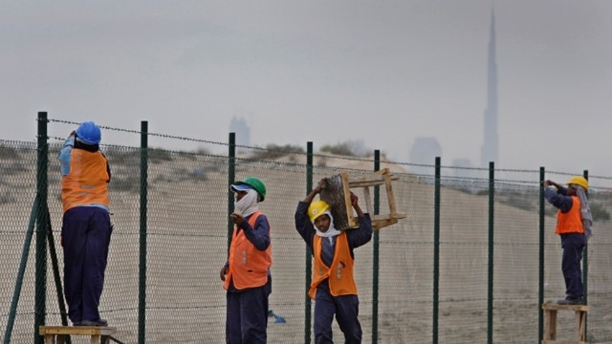 Nov. 27: With a view of world's tallest tower Burj Khalifa in background, Asian laborers fix new fence around a horse race track at Al Barsha district in Dubai.