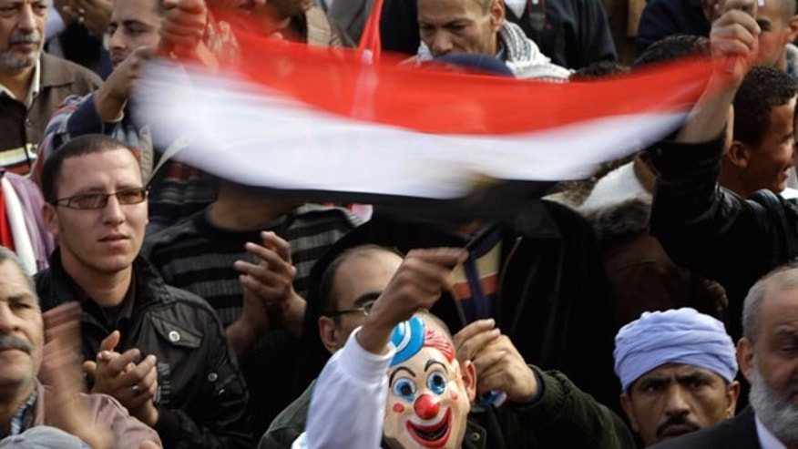Dec. 1, 2011: An Egyptian waves a national flag while wearing a clown mask during a rally in support of the ruling supreme council of the armed forces, SCAF, at Abbasiya Square, in Cairo, Egypt.