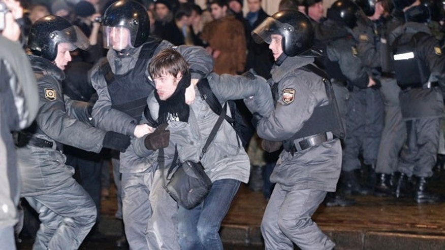 Dec. 5, 2011: Russian police officers detain an opposition member after he and other members marched along one of the central streets in downtown Moscow, Russia.