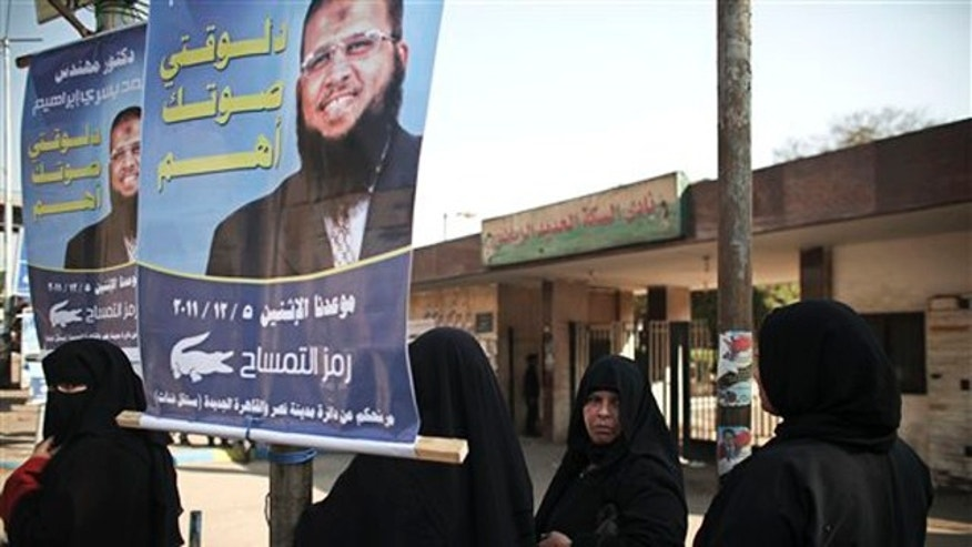 December 5, 2011: Egyptian women stand next to an election poster of Islamist candidate Mohammed Yousri Ibrahim, in Nasr City, a neighborhood of Cairo, Egypt.
