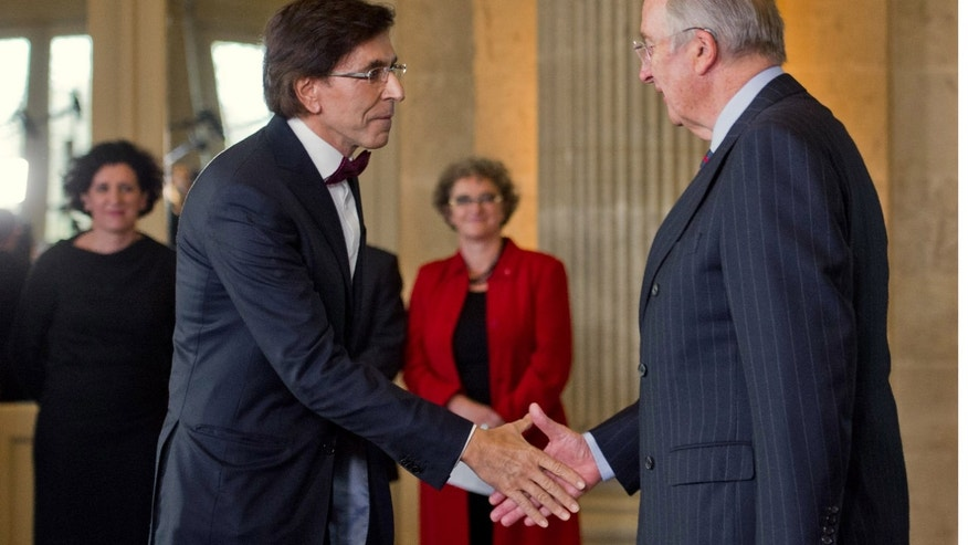 Dec. 6: Elio Di Rupo, left, shakes hands during a swearing-in ceremony with Belgian King Albert II.