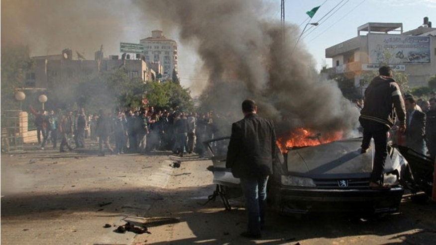 Dec. 8, 2011: Palestinians gather around the wreckage of a car targeted in an airstrike in Gaza City.