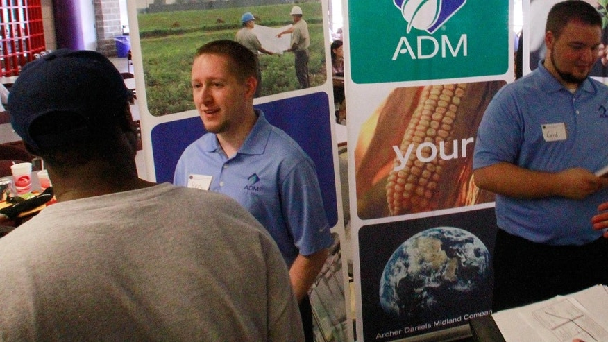 In this Sept. 1, 2011 photo, Archer Daniels Midland Company employees answer questions and hand out job applications during a job fair at the University of Illinois Springfield campus, in Springfield, Ill. The number of people seeking unemployment benefits fell last week to the lowest level in nine months, evidence that the job market is improving. (AP Photo/Seth Perlman)