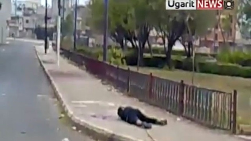 Dec. 9, 2011: Amateur video shows a dead body being dragged by a metal rod in Homs, Syria.