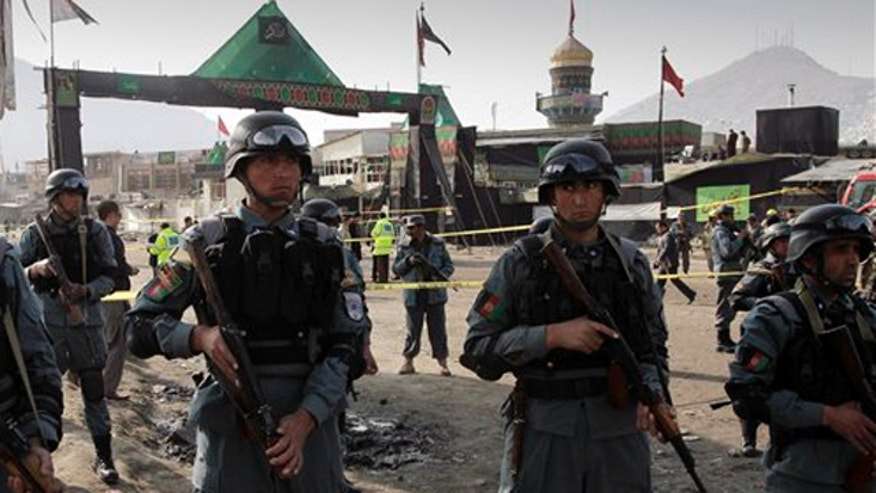 December 6, 2011: Afghan police officers stand guard at the scene of a suicide attack in Kabul, Afghanistan.
