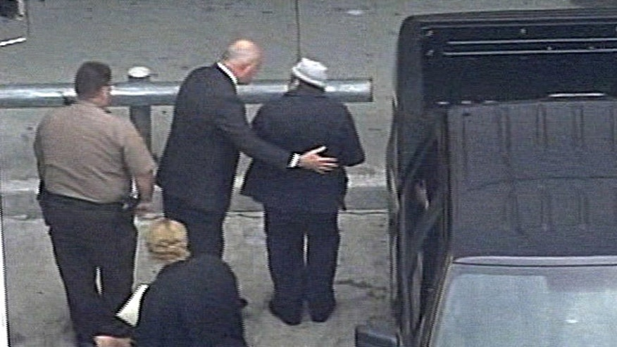 April 10, 2010: In this image from video from WSVN-TV, former Panamanian dictator Manuel Noriega, wearing hat, right, arrives at Miami International Airport in Miami to board an Air France flight to Paris.